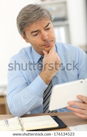 Senior manager in office using tablet - stock photo