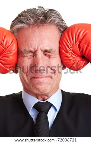 Senior manager pushing red boxing gloves against his aching head - stock photo