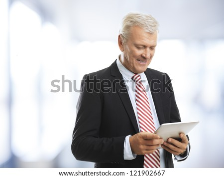 Senior (mature) businessman standing and holding a digital tablet in his hand - stock photo