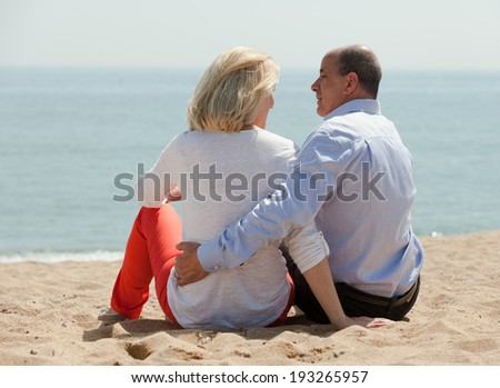 Senior mature couple sitting on beach at seashore and enjoying the view - stock photo