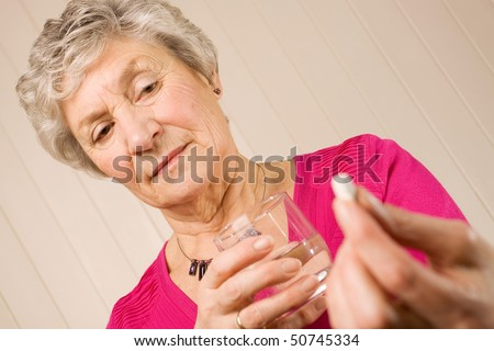 Senior mature lady holding a tablet or pill in one hand and a glass of water in the other - stock photo