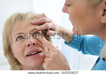 Senior medical check up with focus on eyes examination - stock photo
