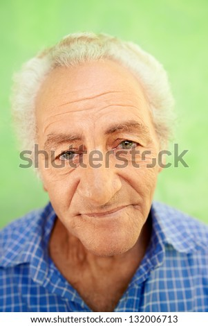 Senior men and feelings, portrait of happy old caucasian man looking at camera on green background - stock photo