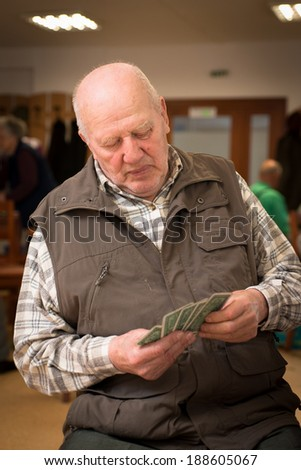 Senior men playing cards indoor - stock photo