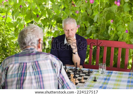 Senior men playing chess in the courtyard - stock photo