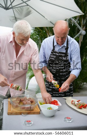 Senior men preparing fish kebabs on a terrace - stock photo