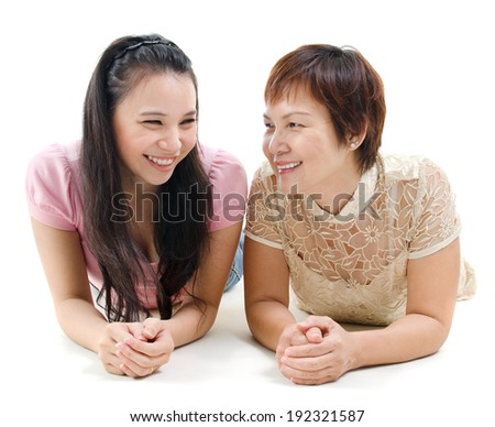 Senior mother and adult daughter lying on floor, having joyful conversation, isolated on white background. Mixed race Asian family portrait.  - stock photo
