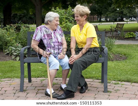 Senior mother and daughter sitting on a bench outside enjoying each others company. - stock photo