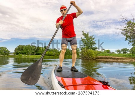 senior muscular male paddler enjoying paddling stand up paddleboard  on a local lake in Fort Collins, Colorado - stock photo