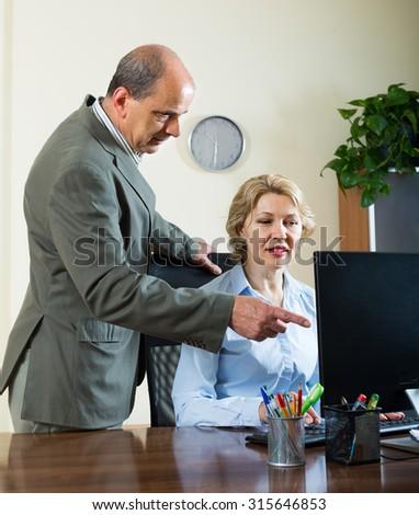Senior office manager scolding aged female secretary for mistake - stock photo