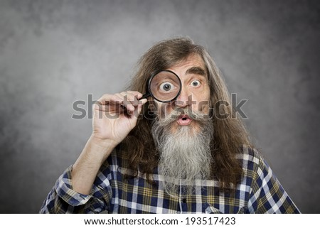 Senior old man looking through zoom magnifying glass. Funny elder amazement investigation or test vision loss - stock photo