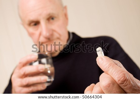 Senior older man holding tablet or pill on one hand and a glass of water - stock photo