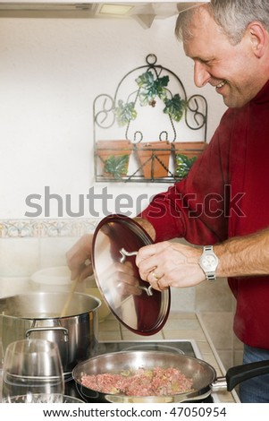 Senior or best ager man cooking dinner in his home kitchen, preparing minced meat in a pan - stock photo