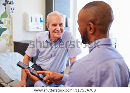 Senior Patient And Doctor Have Consultation In Hospital Room - stock photo