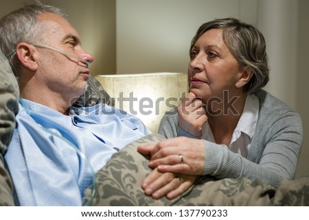 Senior patient at hospital with worried wife holding hands - stock photo