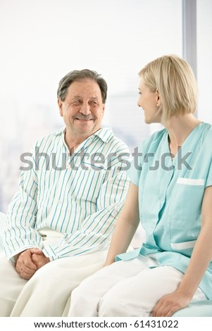 Senior patient in hospital, sitting on bed, chatting to nurse. - stock photo