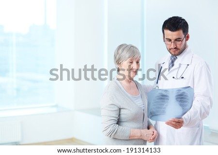 Senior patient looking attentively at x-ray held by radiologist in hospital - stock photo