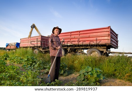 Senior peasant with hayfork standing on the field in front of combine harvesting corn - stock photo