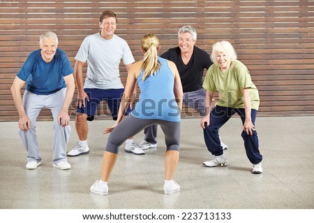 Senior people dancing to music in gym with dance instructor - stock photo