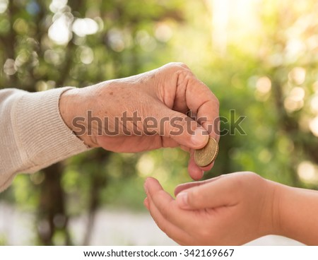 senior people giving coins to children. concept of give money. - stock photo