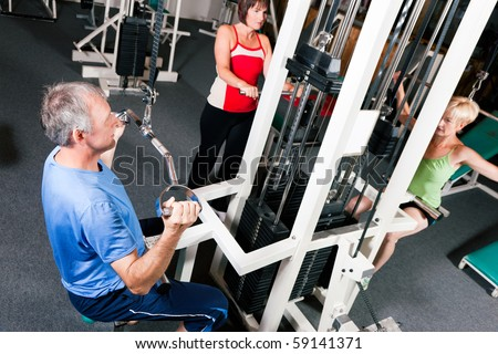 Senior people in a gym exercising on a pulldown machine - stock photo
