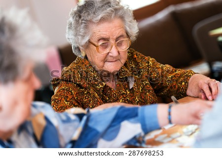 Senior people playing rummy together - stock photo