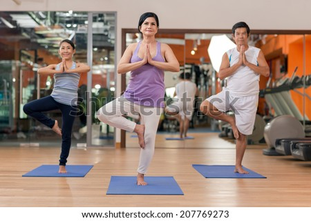 Senior people practicing yoga in the gym - stock photo