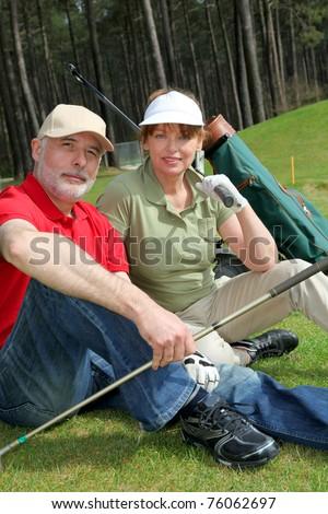 Senior people sitting on golf course - stock photo