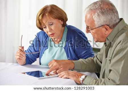 Senior people testing tablet PC with touchscreen in a rest home - stock photo