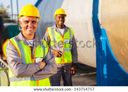 senior petroleum factory worker and african colleague - stock photo