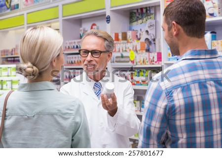 Senior pharmacist explaining the pills to patient at pharmacy - stock photo