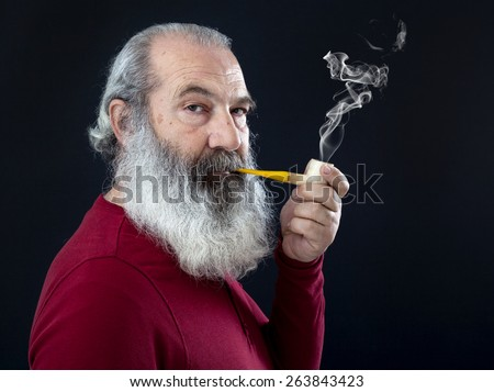 Senior portrait with white beard and pipe - stock photo