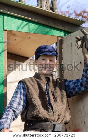 Senior  proudly showing his hunter shack he just finish - stock photo