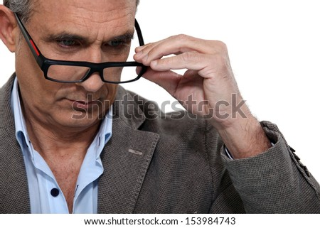 senior putting on his glasses - stock photo