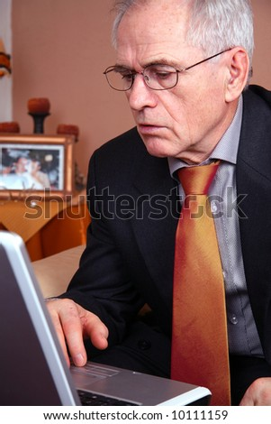 Senior real estate agent looking at his laptop - stock photo