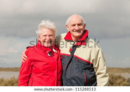 Senior retired couple man and woman enjoying outdoors. Dune landscape with blue cloudy sky. Texel. Wadden island. The Netherlands. - stock photo