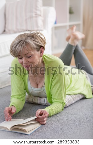 Senior retired woman reading the book in her free time - stock photo