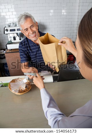 Senior salesman collecting cash while passing grocery bag to female customer at counter in supermarket - stock photo