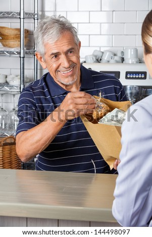Senior salesman giving grocery bag while collecting cash from female customer at supermarket - stock photo
