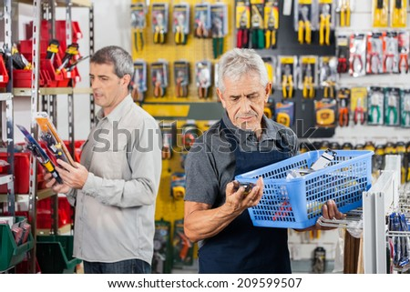 Senior salesman working at hardware store with customer in background - stock photo