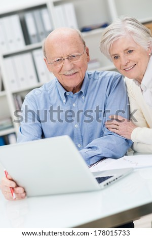 Senior sitting together at a desk in an office couple reading information on a laptop computer - stock photo