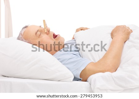 Senior sleeping in a bed and snoring with a clothespin stuck on his nose isolated on white background - stock photo