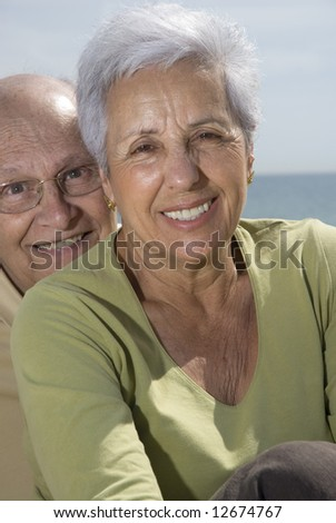 Senior smiling couple with sea in the background. - stock photo