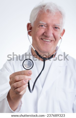 Senior smiling doctor in white protective coat - stock photo