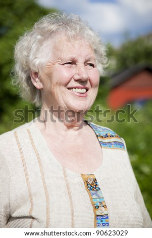 Senior smiling woman looking away in garden - stock photo