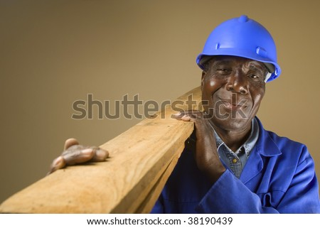 Senior South African or American plumber, carpenter or builder with wooden planks - stock photo