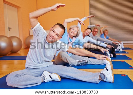 Senior sports class doing stretching exercises in a health club - stock photo