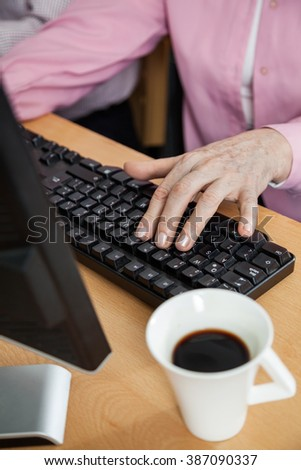 Senior Student Using Computer At Desk In Classroom - stock photo