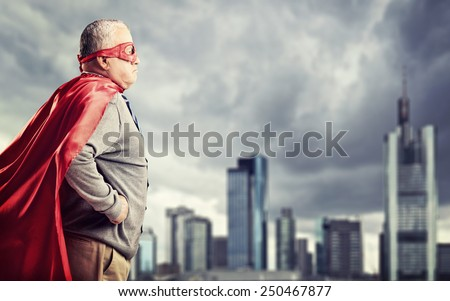Senior superhero standing in front of a dark city  - stock photo