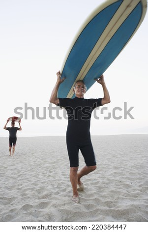 Senior surfers carrying their boards at the beach - stock photo
